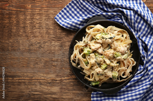Frying pan with delicious chicken Alfredo on wooden table Wallpaper Mural