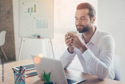 Handsome young business man in white shirt sits at the table in light office and Canvas Print