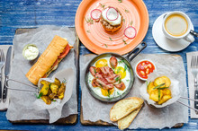 Lunch For Two: Frying Pan With Eggs And Bacon, Potatoes, Sandwich, Sauce And Coffee, Cutlery, On A Blue Denim Background