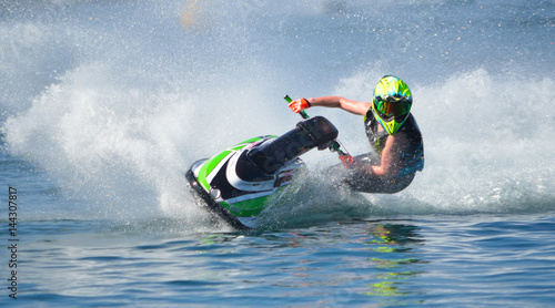 La pose en embrasure Nautique motorise Jet Ski competitor cornering at speed creating at lot of spray.