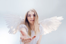 An Angel From Heaven Gives You A Hand. Young, Wonderful Blonde Girl In The Image Of An Angel With White Wings.