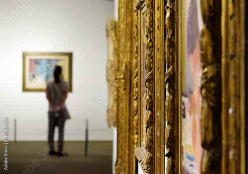 Papel de parede Girl looks at a painting at the Museum of Art