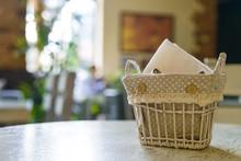 Napkins In Decorative Basket On Restaurant Table