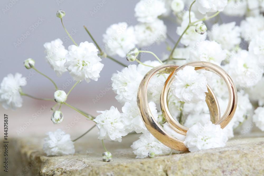 Fototapeta coppia di fedi nuziali in primo piano in mezzo a fiori bianchi