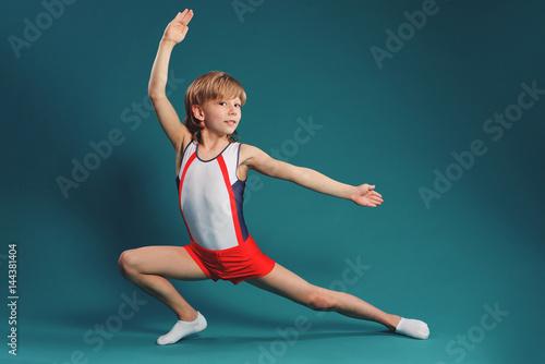 Foto auf Leinwand Gymnastik Happy little boy doing gymnastics isolated on white background