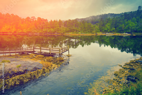 Plakat Skalisty bank spokojna halna rzeka w mglistym jesień ranku. Piękna dzika natura Norwegia. Odbicie na wodzie. Światło słońca