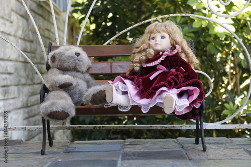 Fotografie, Obraz  Porcelain doll and teddy bear are sitting on the bench