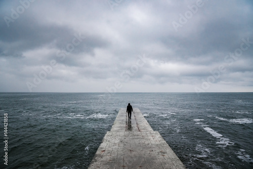 Fototapeta Back view portrait of young man goes to sea on pier