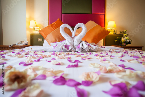 Fotografia  two swans made from towels with flower on honeymoon white bed