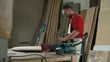Carpenter with various electric sanders polishing a round plank in workshop