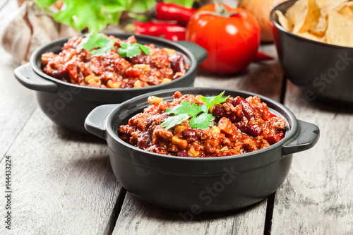 Photo Bowls of hot chili con carne with ground beef, beans, tomatoes and corn