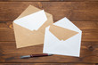Blank paper, envelope on wooden table