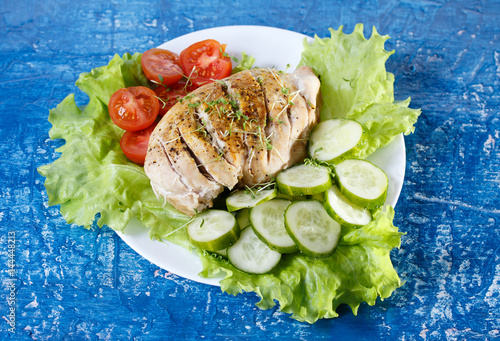 Fotografía  Chicken breast with herbs, tomatoes and cucumbers on blue background