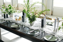 Stylish Meals And A Long Table, Loft. Black Table, Chairs, Dishes, Candles. Banks With Greens, Flowers. Black Candles