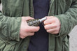 Mężczyzna w wojskowej kurtce z granatem w dłoni