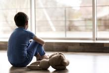 Sad Little Boy Sitting On Floor Beside Window