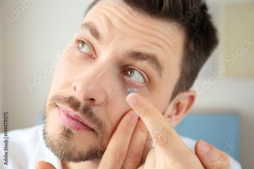 Photo Young man putting contact lenses at home, closeup