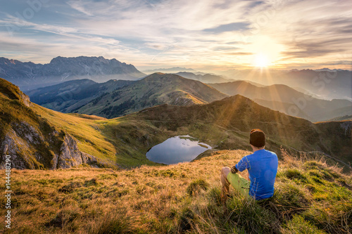 Man sitting on a mountain summit enjoying the view Poster