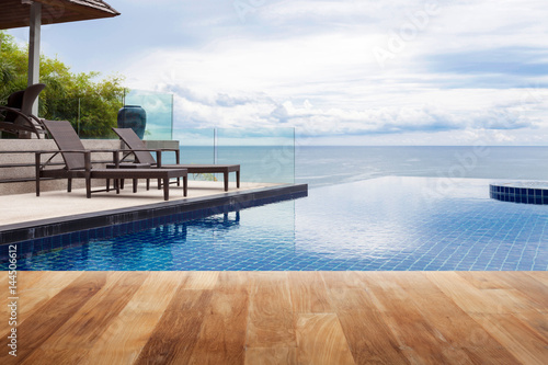 Obraz na płótnie Wood table top on Beach chair in outdoor with swimming pool and sea view andaman sea