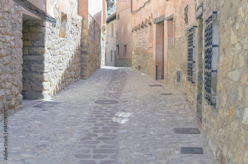 Town of Albarracin, cosidered as spanish national monument, in the province of Teruel (Spain). Alley with stone pavement. Typical reddish houses. Facades with stone. Tourism of Aragon. Rural vacations