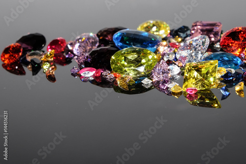 Colorful of different gemstones with space for text on dark background.