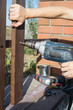 Woman hands drilling wood plank fence to metal construction. Building a wooden fence with a drill and screw.