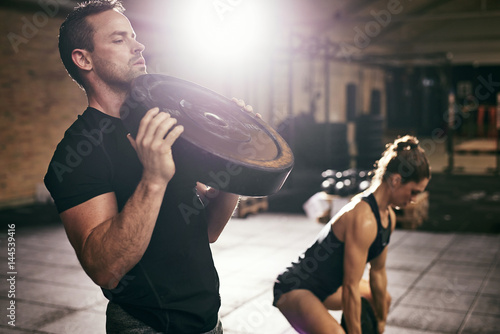 Young sportsmen having workout with weight disks Фотошпалери