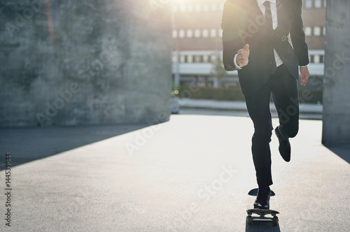 Fotografie, Obraz  Unrecognizable man in suit riding a skateboard