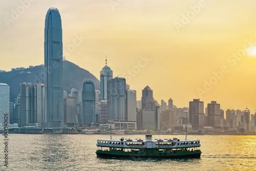 Star ferry at Victoria Harbor and Hong Kong skyline at sundown Poster