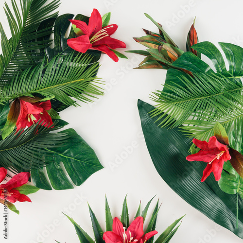 Foto  Creative layout made of tropical palm leaves and colorful flowers