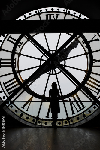 Poster Paris Woman silhouette standing in front of large clock