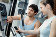 Trainer helping woman on exercise stepper machine.