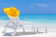 Straw yellow sunhat on chaise lounges