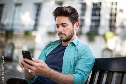 Tourist sitting on bench in London looking at smartphone