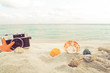 The concept of leisure travel in the summer on a tropical beach seaside. retro camera on the sandbar with starfish, shells, coral on sandbar and blur sea background. vintage color tone styles.