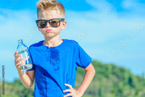 Fotografía  Portrait of a thirsty handsome boy in sunglasses drinking water on the desert tr