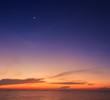 Orange sky over sea shore and silhouette shell farm