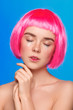 Woman with pink hairdo with eyes closed
