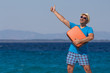 Man holding luggage and showing thumbs up against the blue ocean. Travel concept