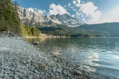 Poster Reflexion Alpine mountain range with beautiful lit mountains in the background and the Eibsee lake in the foreground