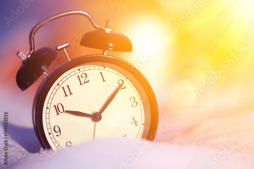 Fotomagnes Staromodny budzik w śniegu z ranku światła słonecznego zakończeniem up