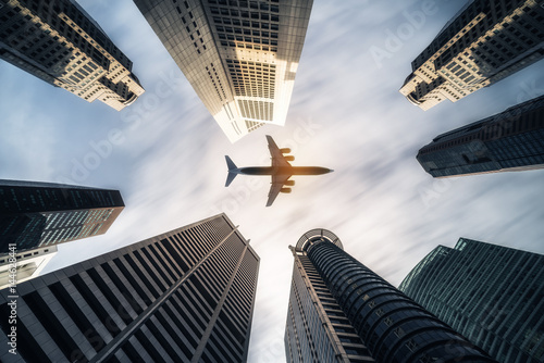 Airplane flying over city business buildings, high-rise skyscrapers Wallpaper Mural