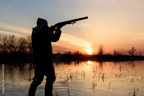 Foto op Canvas Jacht Silhouette of a hunter at sunset in the water with a gun.