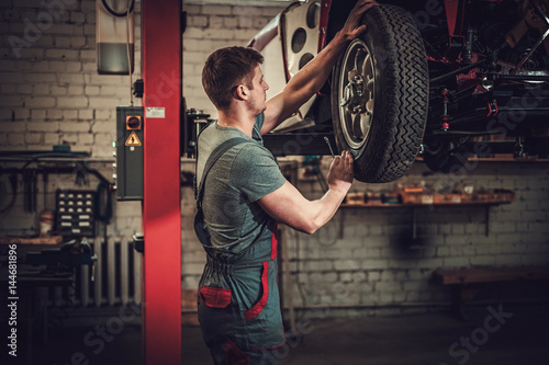 Fotomural  Mechanic working on classic car wheels and suspension in restoration workshop