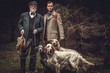 canvas print picture - Two hunters with dogs and shotguns in a traditional shooting clothing.