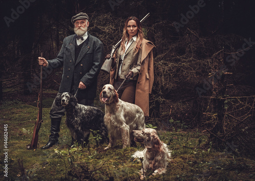 Photo Two hunters with dogs and shotguns in a traditional shooting clothing