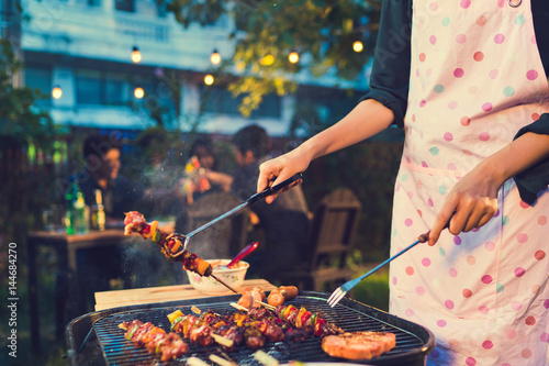 Fotografía Asian woman are cooking for a group of friends to eat barbecue