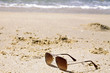 Sunglasses on sand beach with sea background