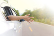 Woman hand at the car window on an country road