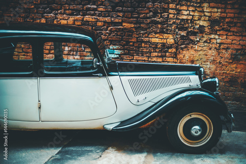 Cadres-photo bureau Vintage voitures Side view of noname luxury retro vintage car with curved forms, black and white colours, in front of orange grunge brick wall